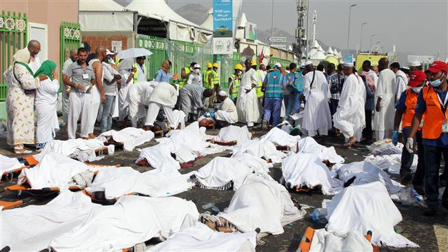 Saudi emergency personnel and Hajj pilgrims stand near the bodies covered in sheets at the site of a crush in Mina, near the holy city of Mecca, in Saudi Arabia, September 24, 2015. (AFP)