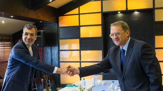 Hossein Jaberi Ansari (L), the Iranian deputy foreign minister for Arab and African Affairs, shakes hand with Russian Deputy FM Mikhail Bogdanov before bilateral talks in Tehran, August 15, 2016.
