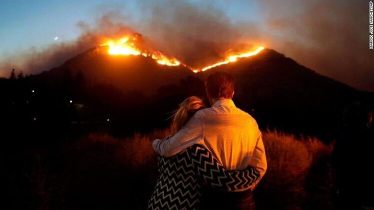 A couple hugging on Nov. 9 as they watch a wildfire on a Los Angeles hilltop / Photo by AP