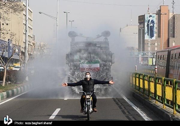 A cyclist riding his motorcycle in front of a truck disinfecting the city of Tehran