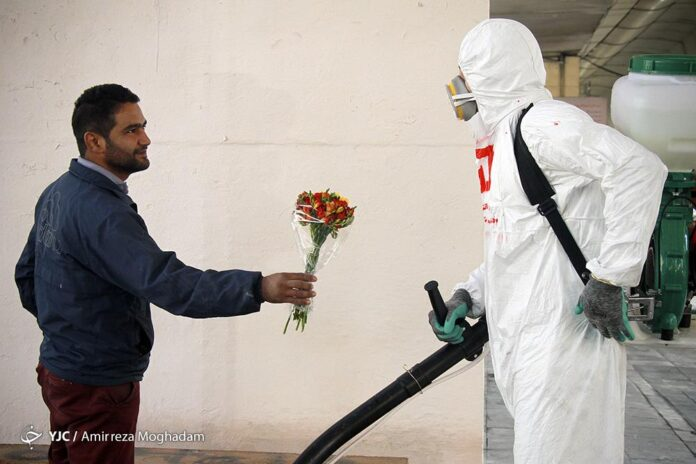 Citizen Giving Flower to Firefighter Disinfecting Tehran